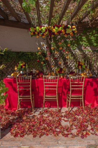 Outdoor tablescape with red tablecloth and red and orange roses hanging from chandelier