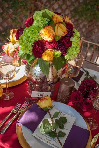 Red table cloth with white plates and purple napkins with a yellow rose on top