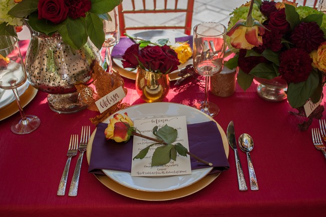 Red tablecloth, white plates and purple napkins, yellow rose on top
