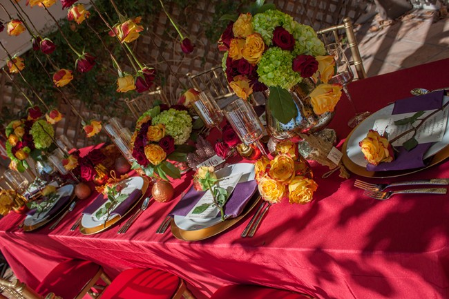 Outdoor fall wedding reception table with red table cloth, purple napkins and green, red and yellow flowers