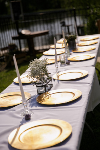 A long rectangle table for backyard wedding reception with gold chargers and white table cloth