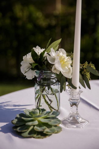 Clear mason jar with white flowers beside a crystal candle holder with white candle