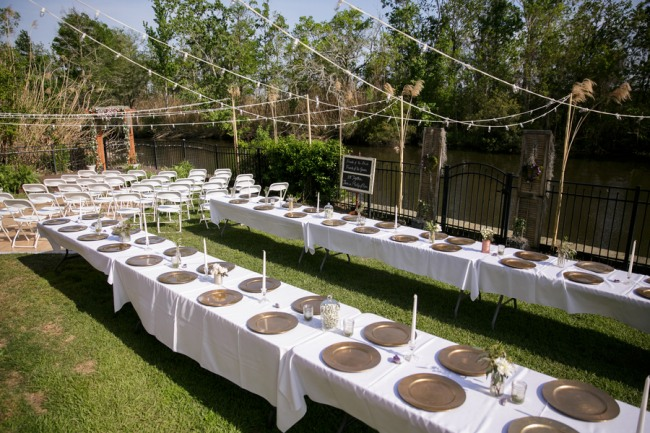 Long white rectangle tables with gold chargers for backyard wedding reception
