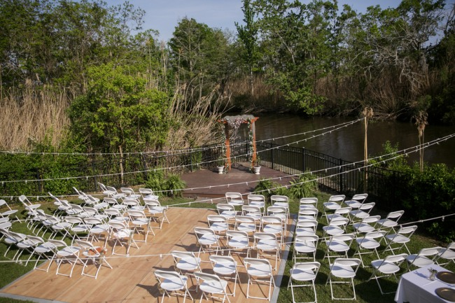 Intimate wedding ceremony in a backyard using white plastic chairs