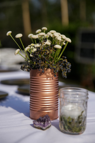 bronze tin can used for a flower vase holding white and purple flowers