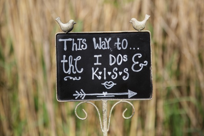 "Wedding decor chalk board sign with ""This way to the I dos and kiss"""