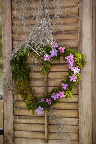A heart wreath made out of moss and purple flowers
