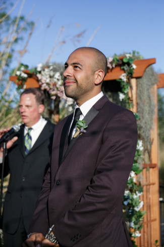 Groom standing at the alter with a big grin wearing a black skinny tie