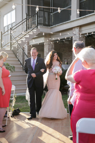 Bride wearing a pink dress walking down the aisle with father