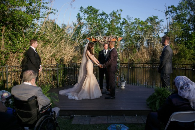 Bride and groom standing at the altar holding hands in backyard wedding