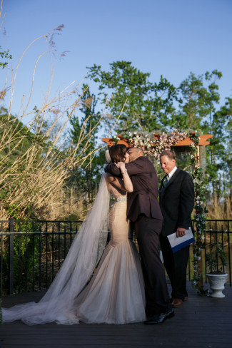 Bride wearing pink gown kissing groom after wedding ceremony in backyard wedding