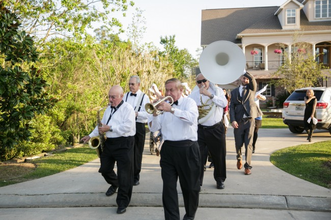 A band wearing white shirt and bow ties playing down the driveway of a private residence
