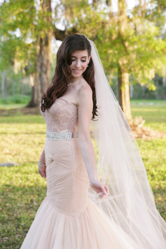 Bride wearing a pink veil and gown standing in the grass and looking down