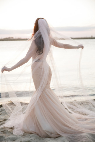 Bride standing on the beach with her back turned to the camera wearing a pink gown and veil