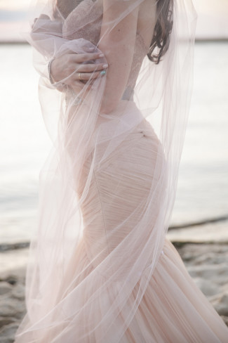 Bride's pink veil wrapped around her on the beach