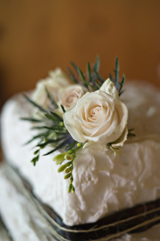 Top of tier of white wedding cake with brown ribbon and twine and a white rose