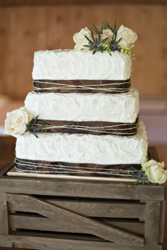 1 tier white wedding cake with brown ribbon and twine and white roses and purple thistles