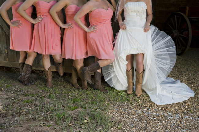 Bridesmaids wearing pink strapless dresses standing with bride all wearing cowboy boots