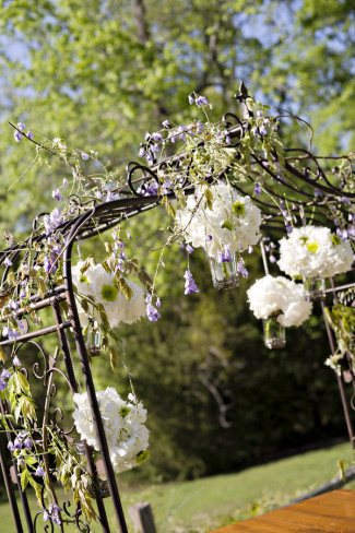 Wedding ceremony backdrop with purple flowers and white hydrangeas hanging from arbor