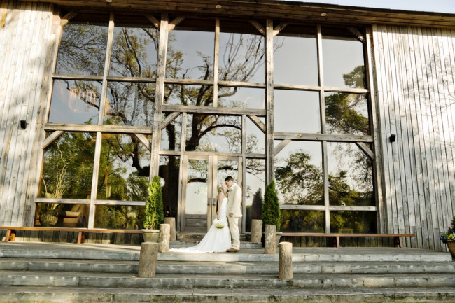 Bride and groom standing on stairs of Fair Weather Farms wedding venue