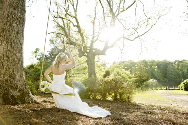 Bride sitting on swing with back turned to the camera and sun shining in the back ground
