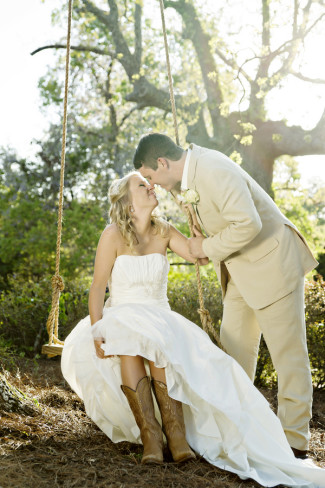 Bride sitting on swing wearing cowboy boots while grooms leans over her to kiss her.