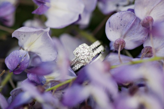 halo engagement ring with wedding band placed in purple flowers
