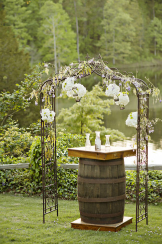Wedding ceremony by lake with arbor and wine barrel for a table for the sand ceremony