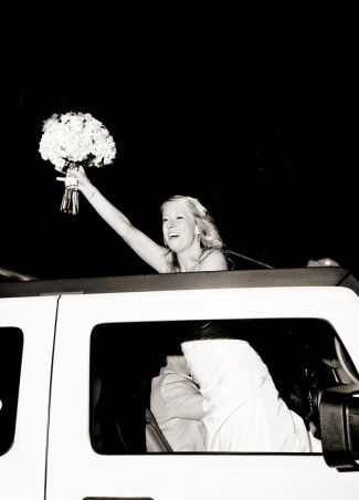 Bride standing up through trucks sun roof waving her bouquet and saying goodbye