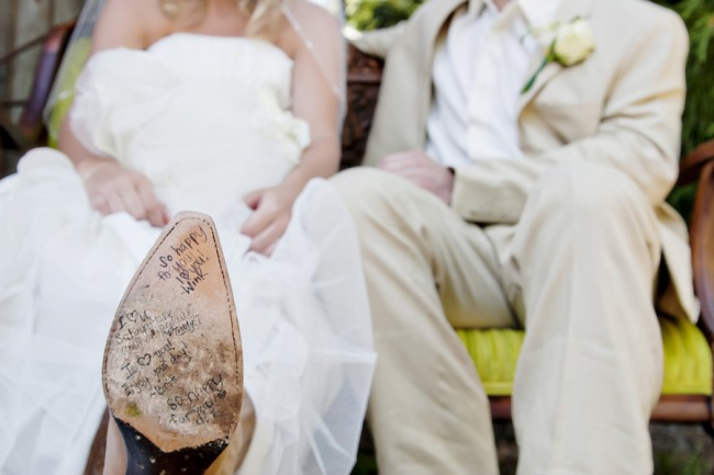 Bride showing off the bottom of her cowboy boot that has signatures on the bottom
