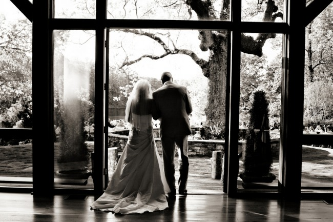 Black and white photo of bride and her father walking down the aisle during outdoor wedding ceremony