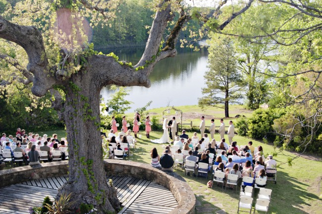 Arial shot of an outdoor wedding with a big tree and in front of a lake