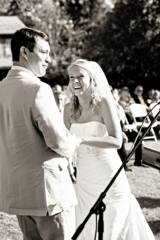 Bride and groom holding hands and laughing during wedding ceremony