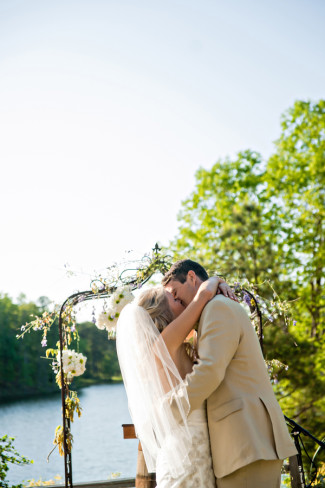 Bride and groom kissing during wedding ceremony in front of lake