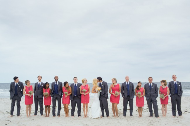 Bride and groom kissing on beach with bridal party in coral and grey