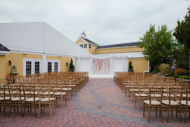 wedding ceremony at bridgeview Yacht Club in front of a yellow building