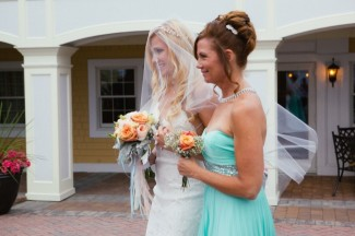 Mother in teal walking bride down the aisle