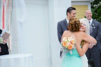 Mother in teal hugging bride at the altar