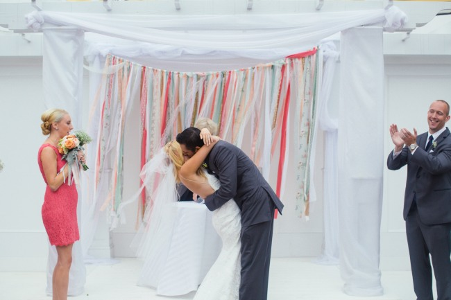 Bride and groom kissing during wedding ceremony in front of colorful coral and blue backdrop