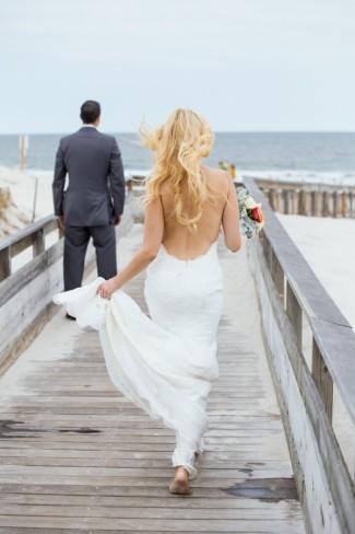 Bride walking towards groom on boardwalk in bare feet for first looks