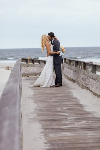 Bride and groom kissing on wooden boardwalk during first looks