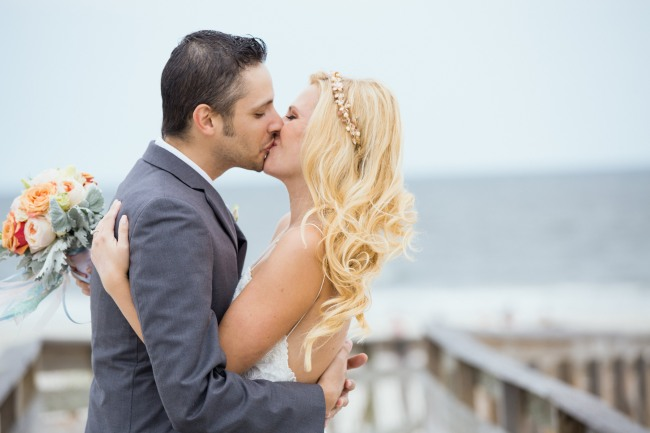 Bride and groom kissing on wooden boardwalk at Bridgeview Yacht Club