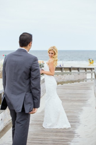 Bride wearing spaghetti strap dress looking at groom in grey suit on boardwalk