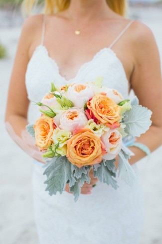 Bride holding peach roses and pink peonies bouquet
