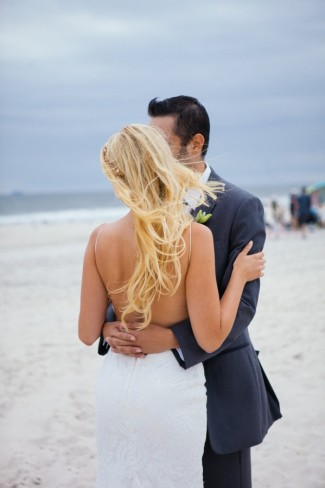 Bride and groom embracing and looking out to the Atlantic ocean