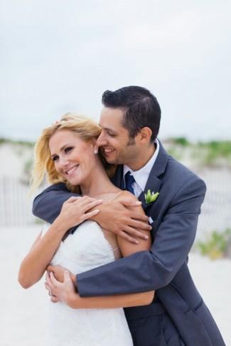 Bride and groom embracing on the beach after ceremony at Bridgeview Yacht Club Wedding