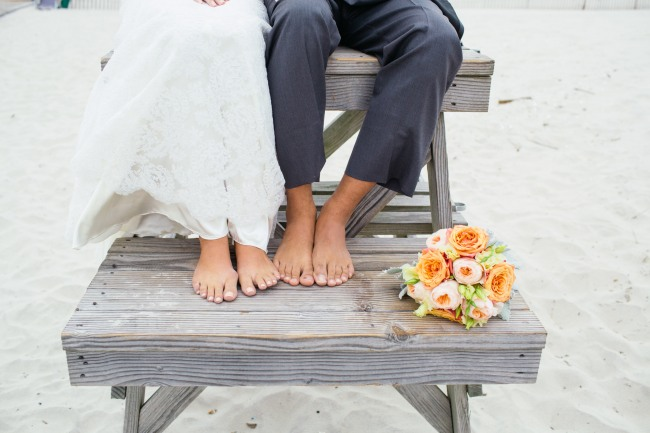 Picture of the feet of a Bride and groom sitting on a lifeguard stands on a beach