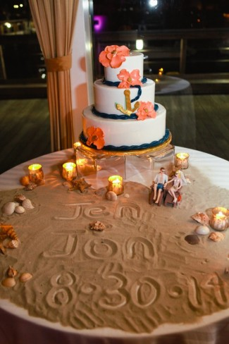 Nautical coral and navy blue wedding cake on a table with sand