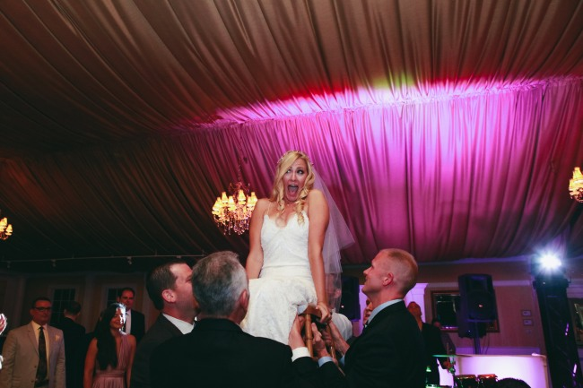 Bride being lifted in the air on a chair on the dance floor