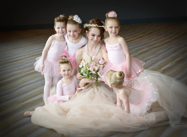 Bride wearing a chapel length veil sitting with baby ballerinas